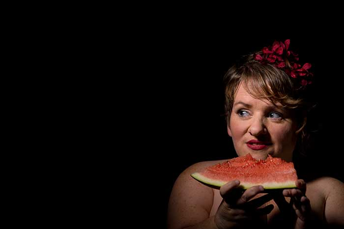 Photograph of Caroline Bowditch. The background is black. Caroline is on the right side of the photo. She is wearing red flowers in her hair and red lipstick. She is looking over to the left and holds a piece of watermelon with a bit out of it. Her face is lit. Her bare shoulders and her hands are in shadow.