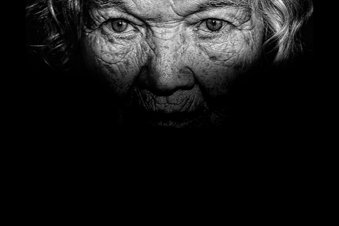 black and white image of the partly-lit face of an old white woman. Her eyes are the main focus of the shot.