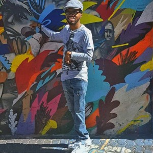 A colour photograph of Nolan Stevens standing near a wall covered in street art. He is wearing a light-blue peak cap and pointing to the wall.