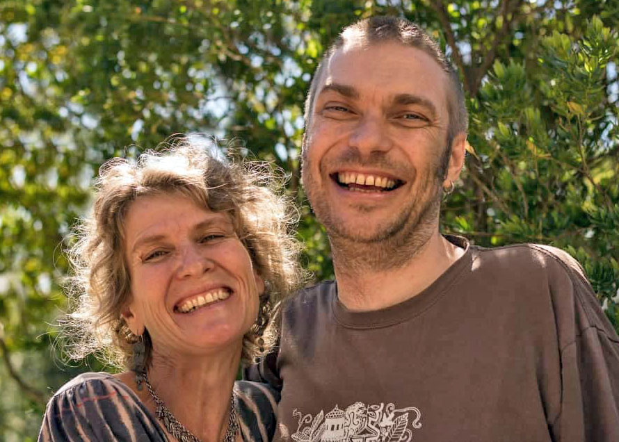 Colour photograph of Robyn, on left of image. She has blonde hair and is laughing. Andrew is next to her. He is taller and has his arm around Robyn. He is also laughing. They are standing in front of trees. Photo taken by Maureen Miller