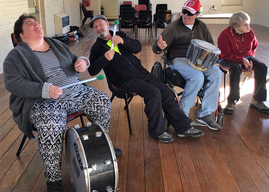 Colour photograph of Eurobodalla School of Possibilities, Beat Garden participants sitting a hall with drums. They are laughing. Photograph by Tim Burke.