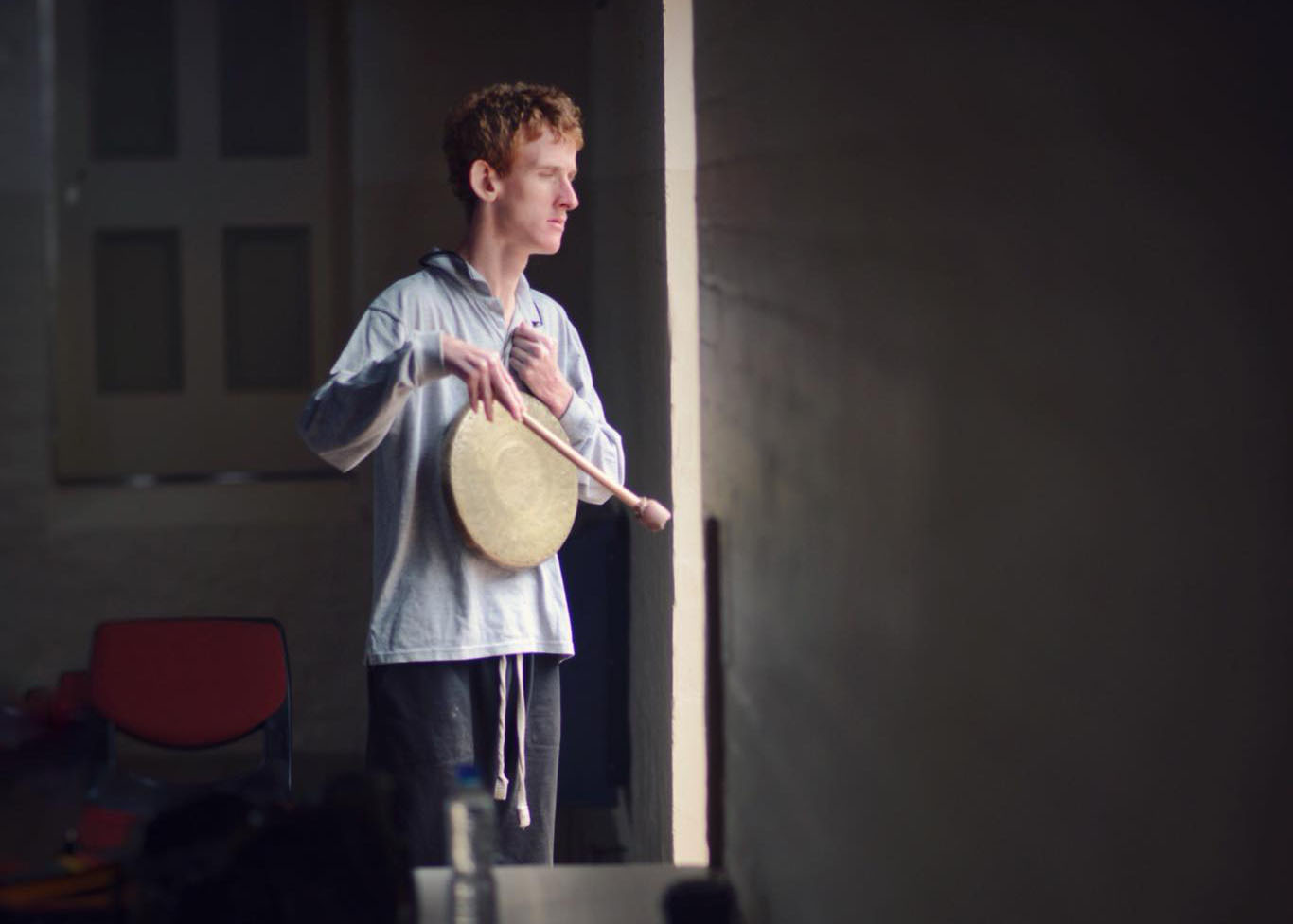 Colour photograph of Eurobodalla School of Possibilities, Beat Garden participant standing by a door way looking out. He is playing a drum. Photographer: Tim Burke.
