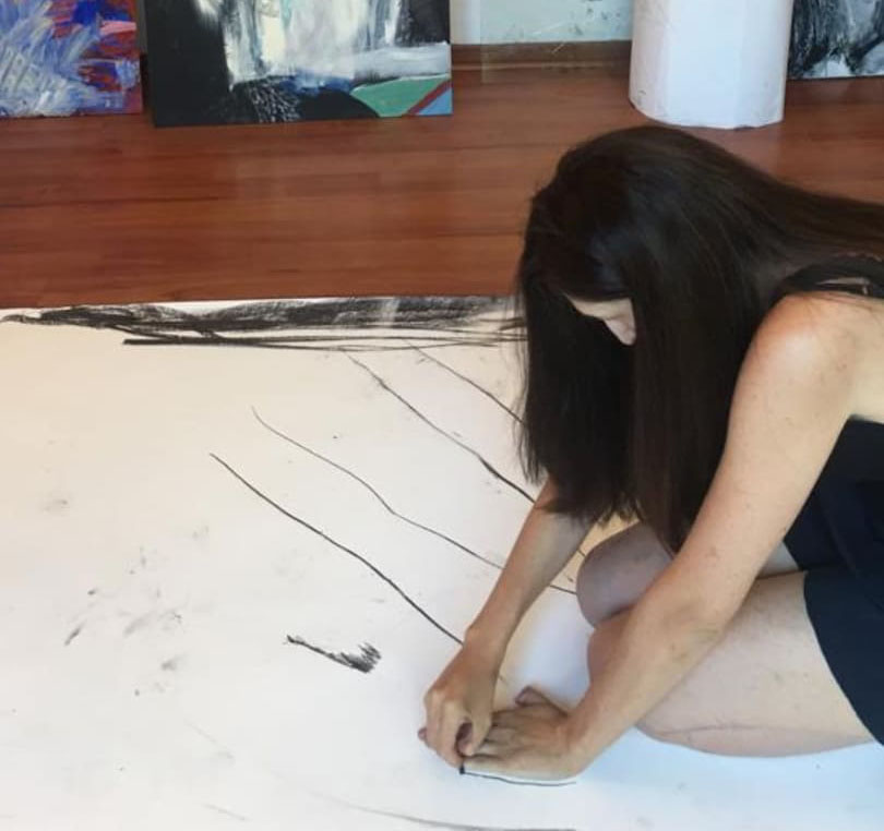 Alexandra Makhlouf sitting on a large piece of paper and drawing around her hand. There a black marks on the paper and some smudges.
