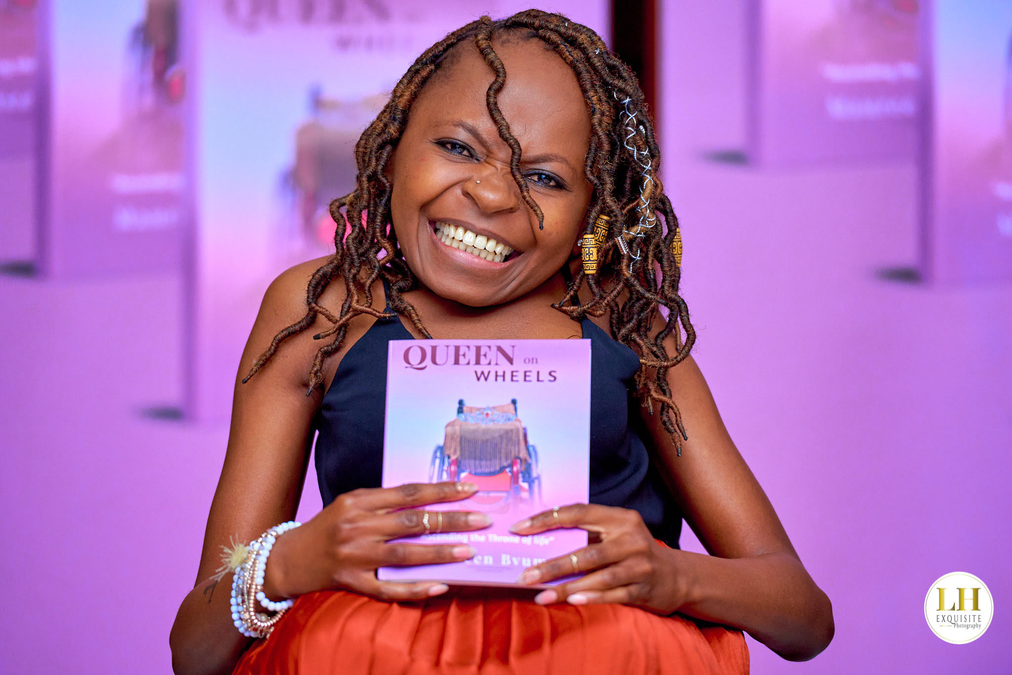 Photo: Maureen Bvuma wearing orange skirt and sleeveless navy top. Her hair is braided. She is sitting, smiling and holding her book 'Queen on Wheels'