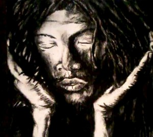 The Dreaded Thinker by Nolan Stevens. Black and white image of a man with dread locks, looking downwards with his chin resting in his hands.