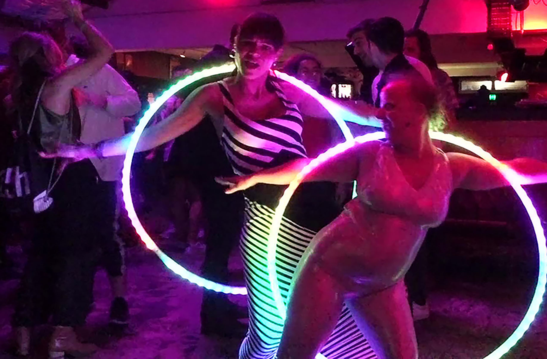 two people dancing with hula hoops at a club. People are dancing in the background.
