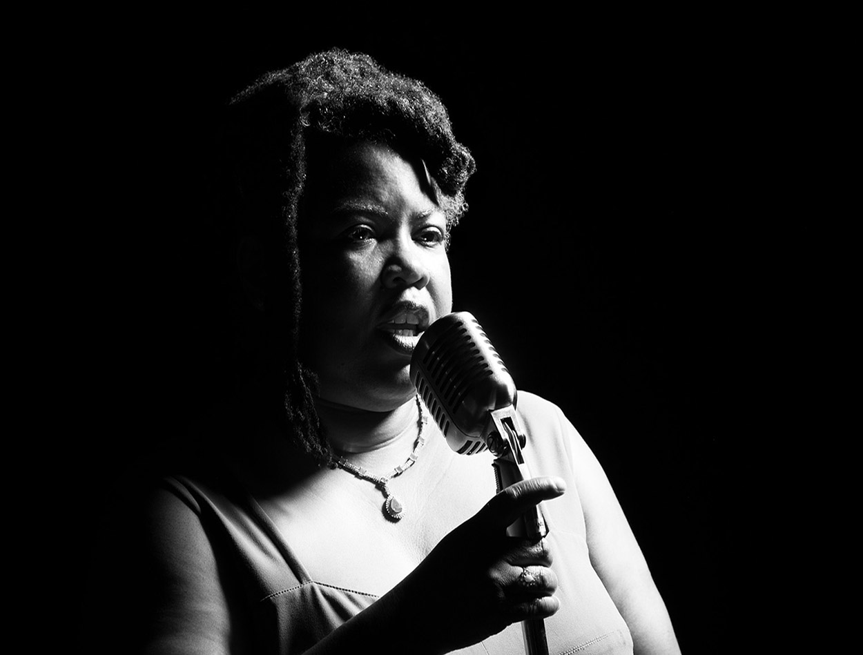 A black woman talking or singing into a mic on stage