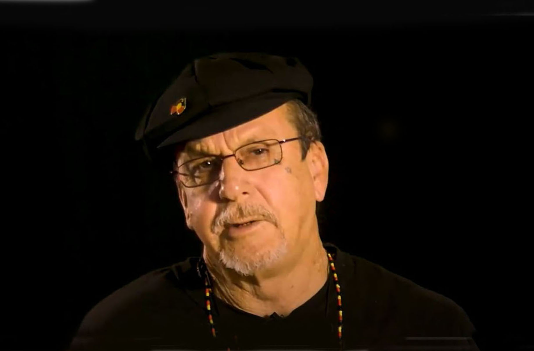 Ken Canning wearing a black cap, black t-shirt, necklace and badge in Aboriginal colours